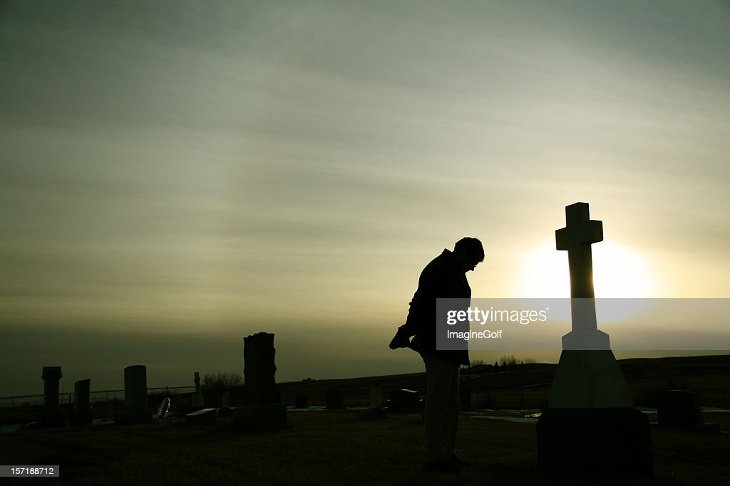Silhouette of Caucasian Man Mourning at Graveyard