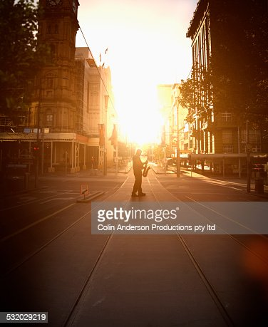Silhouette of Caucasian musician holding saxophone on city street at sunrise