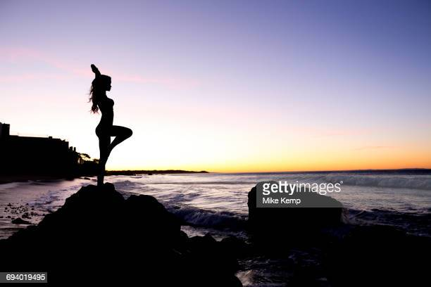 Silhouette of Caucasian woman balancing on rock at beach