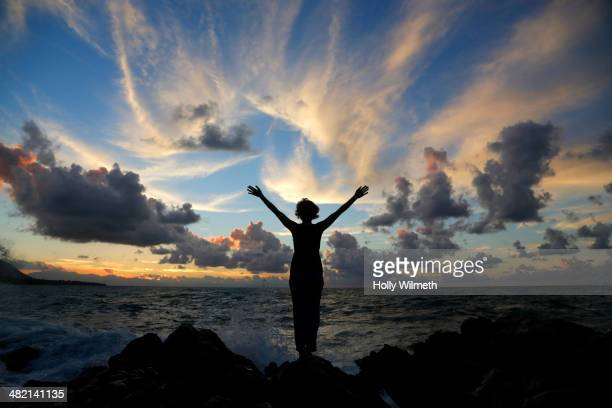 Silhouette of Caucasian woman on beach at sunset