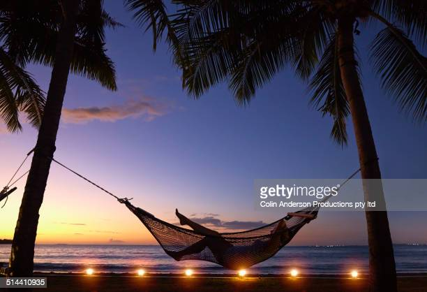 Silhouette of Caucasian woman relaxing in hammock at sunset