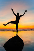 Silhouette of cheerful balancing on stone in water funny man at spectacular sunset background. Multicolored vibrant vertical outdoors image with ocean horizon.