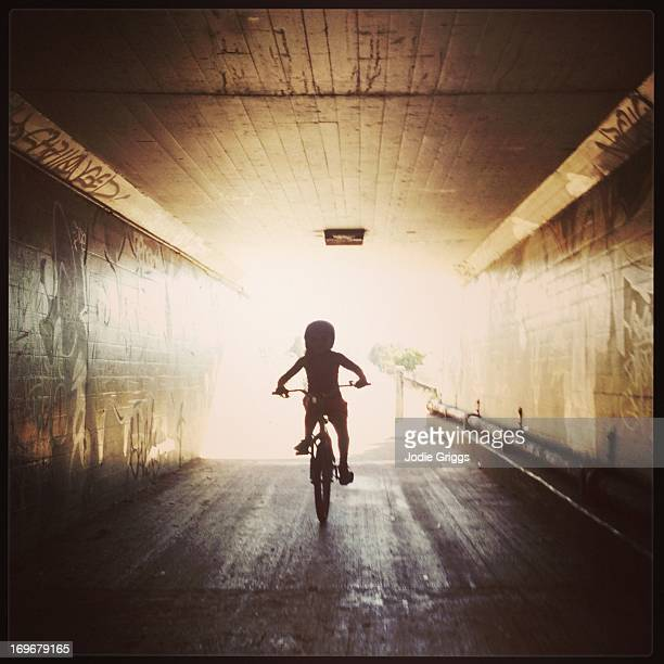 Silhouette of child riding bike through tunnel