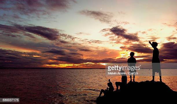 Silhouette Of Children Against Sea And Moody Sky At Sunset