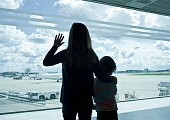 Silhouette of children waving at airport