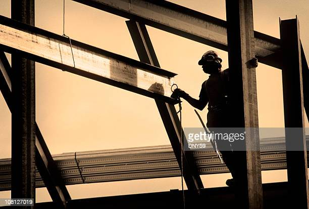 Silhouette of Construction Worker Working on Frame