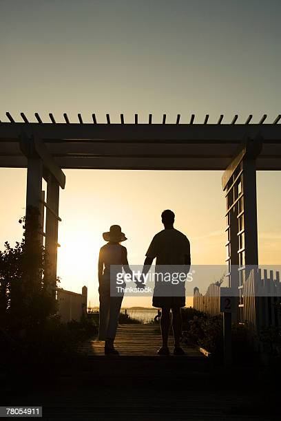 Silhouette of couple holding hands at sunset under veranda