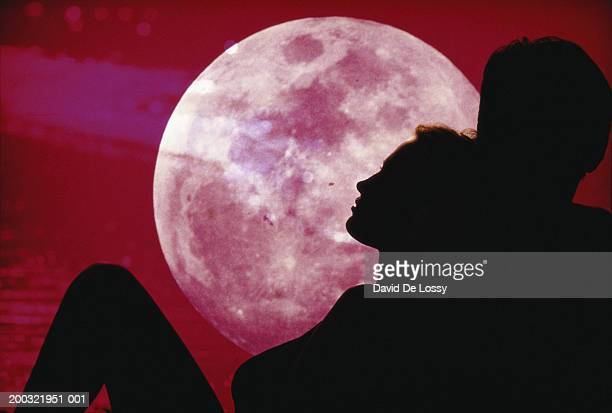 Silhouette of couple, moon in background
