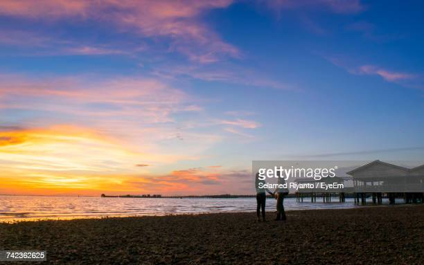 Silhouette Of Couple On Beach Against Sky During Sunset