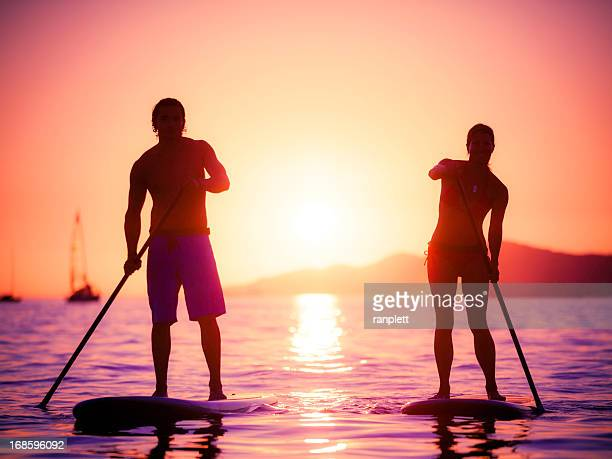Silhouette of couple on stand-up paddle boards