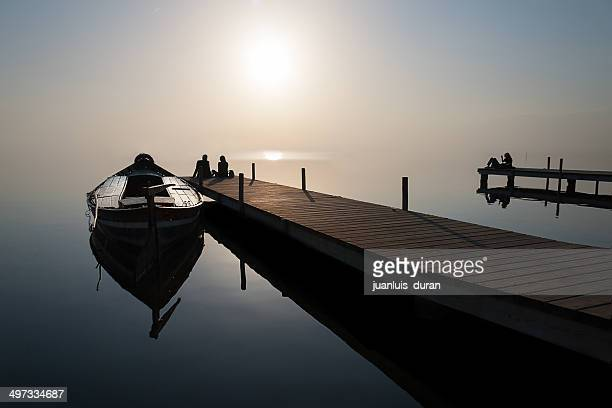 Silhouette of couple sitting at end of jetty by moored boat