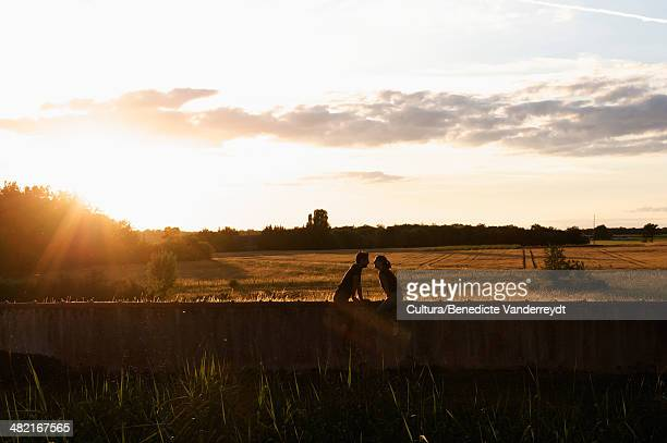 Silhouette of couple sitting on wall