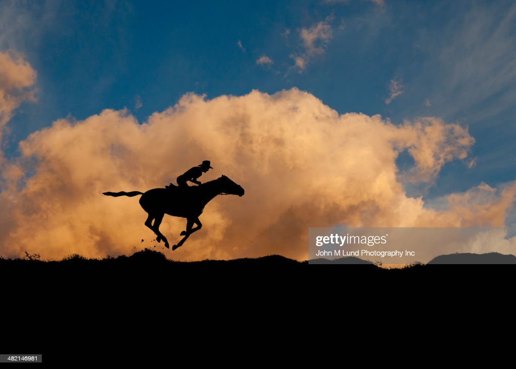 Silhouette of cowboy riding horse against blue sky and clouds