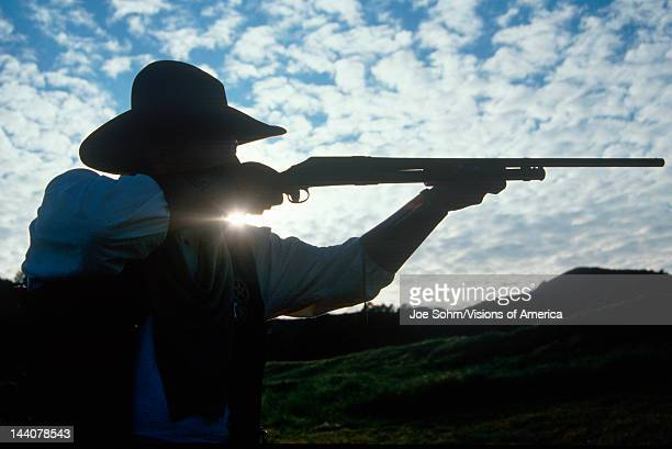 Silhouette of cowboy shooting rifle