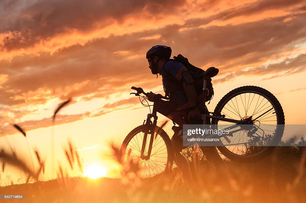 Silhouette of cyclist climbing the mountain