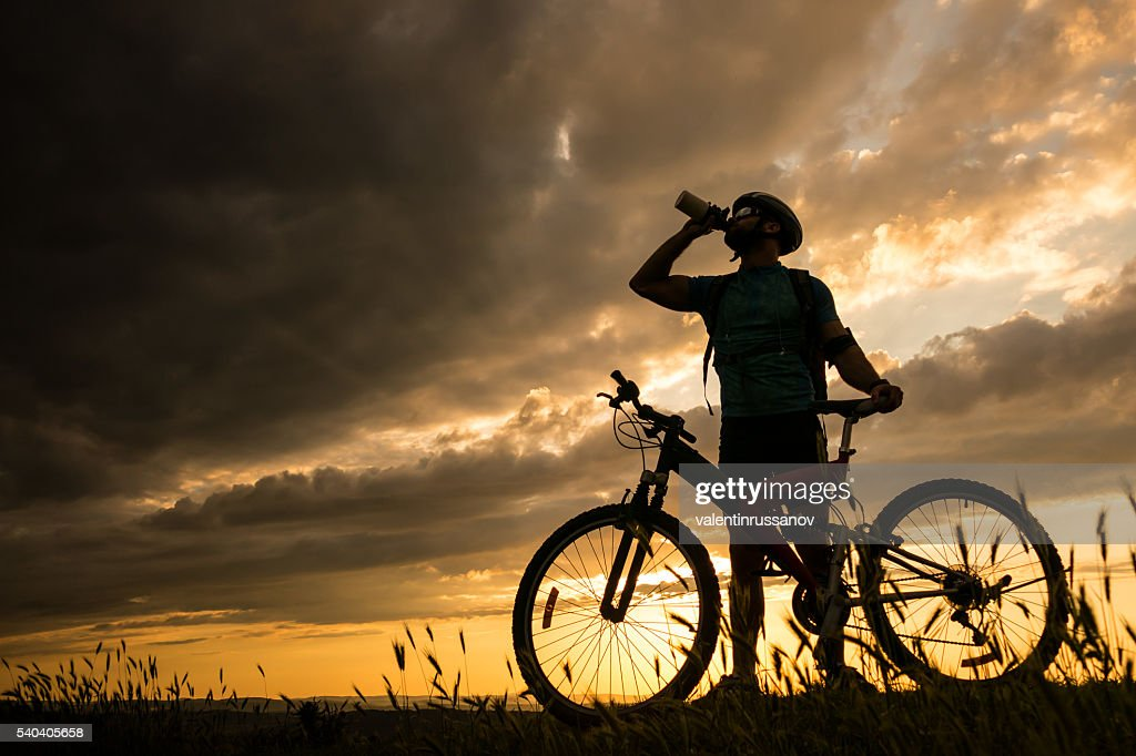 Silhouette of cyclist drinking water on the top of mountain