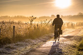 Silhouette of senior cyclist through hazy early morning rural landscape at sunrise