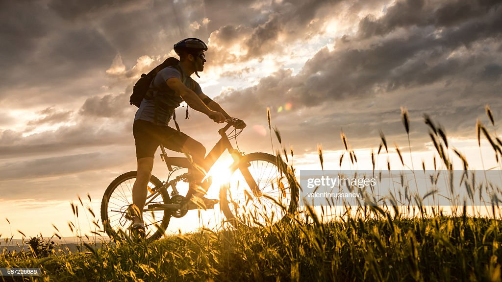 Silhouette of cyclist moving up on the mountain
