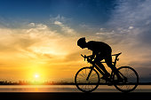 Silhouette of cyclist on the background of beautiful sunset,Silhouette of man ride a bicycle in sunset background.