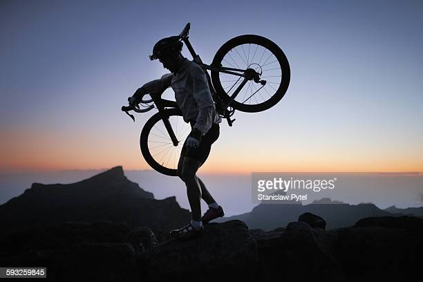 Silhouette of cyclist with bicycle in mountains