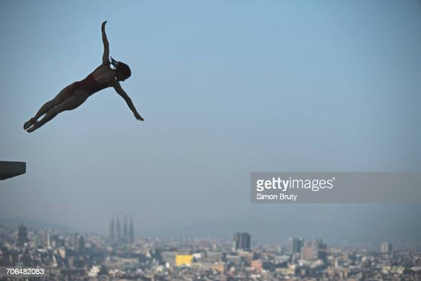 Silhouette of diver Tracey Miles of Great Britain is captured high over the Sagrada Familia of Antoni Gaudí during a diving competition prior to the...
