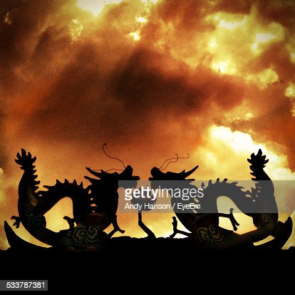 Silhouette Of Dragons Against Dramatic Sky