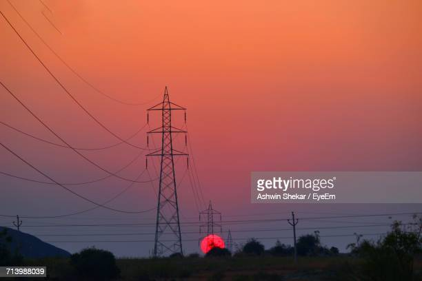 Silhouette Of Electricity Pylon Against Cloudy Sky During Sunset