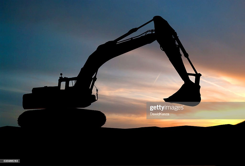 silhouette of Excavator loader at construction site with raised : Stock Photo