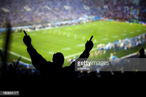 Silhouette of excited fans at football game