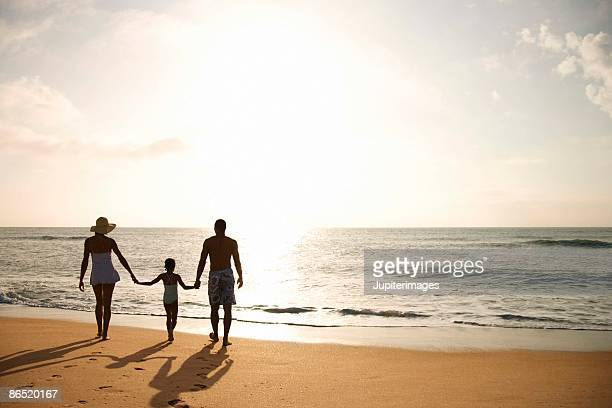 Silhouette of family walking on beach