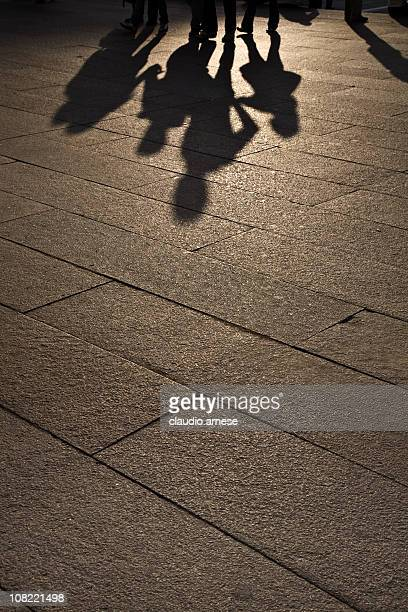 Silhouette of Family Walking on Sidewalk, Low Light. Color Image