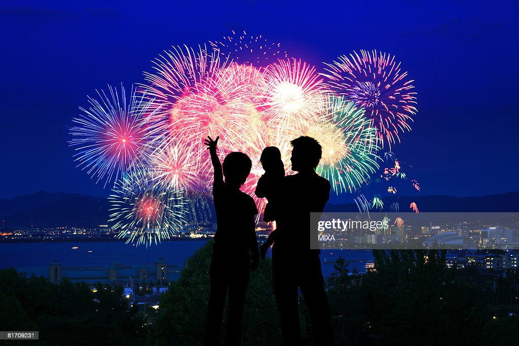 Silhouette of family watching firework display : Stock Photo