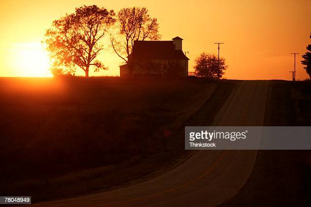 Silhouette of farmhouse at sunset