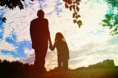 silhouette of father and daughter holding hands at sunset nature