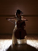 Silhouette of female cellist playing cell on stage