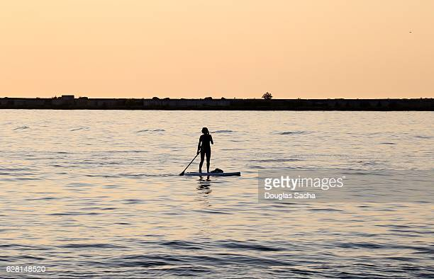 Silhouette Of Female Paddleboarding In the water Against the Morning Sky
