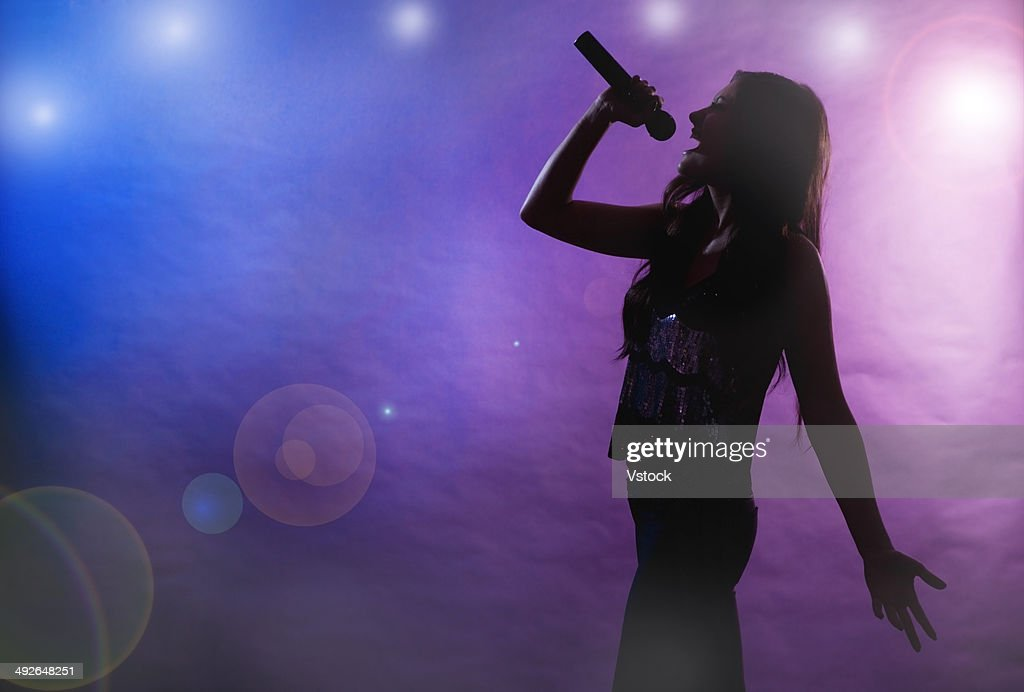 Silhouette of female singer on stage