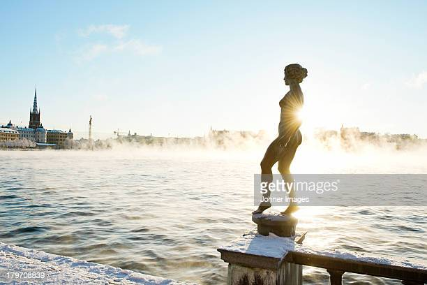 Silhouette of female statue with Stockholm cityscape in background
