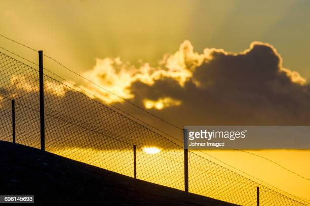 Silhouette of fence at sunset