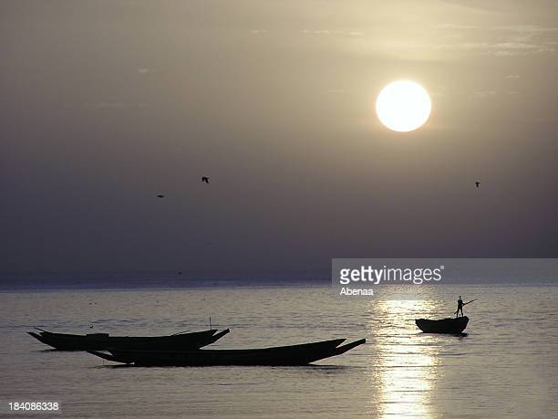 Silhouette of fisherman fishing at sunset