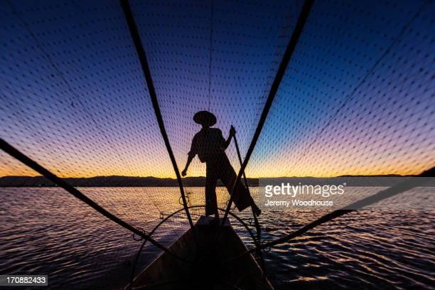 Silhouette of fisherman rowing canoe on water