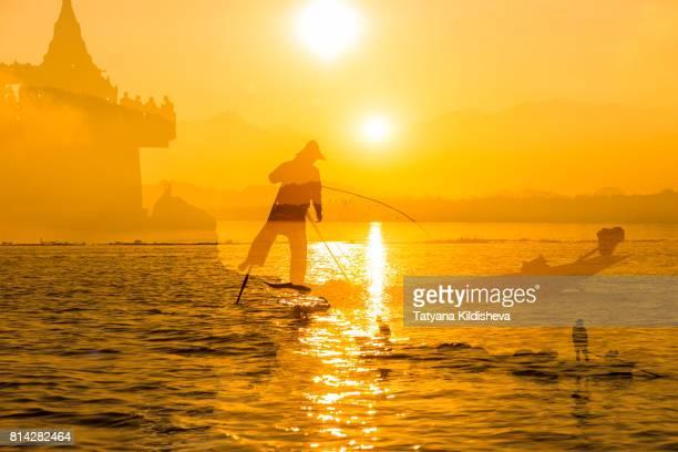 Silhouette Of Fishermen Against Orange Sky During Sunset Multiple Exposure