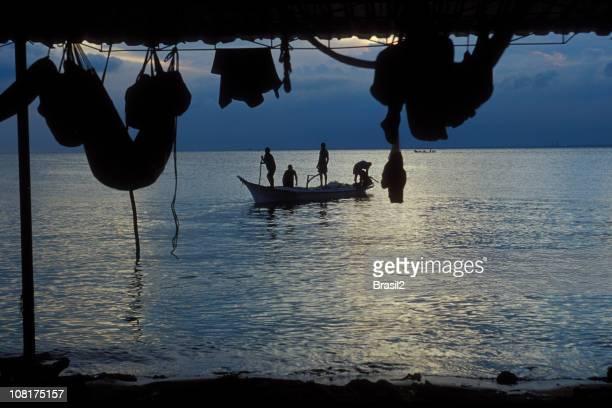 Silhouette der Fischer auf einem Boot bei Sonnenaufgang