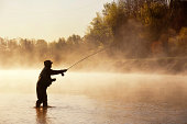A fly fisherman fishes for Striped Bass in the early morning fog on a river in Nova Scotia.