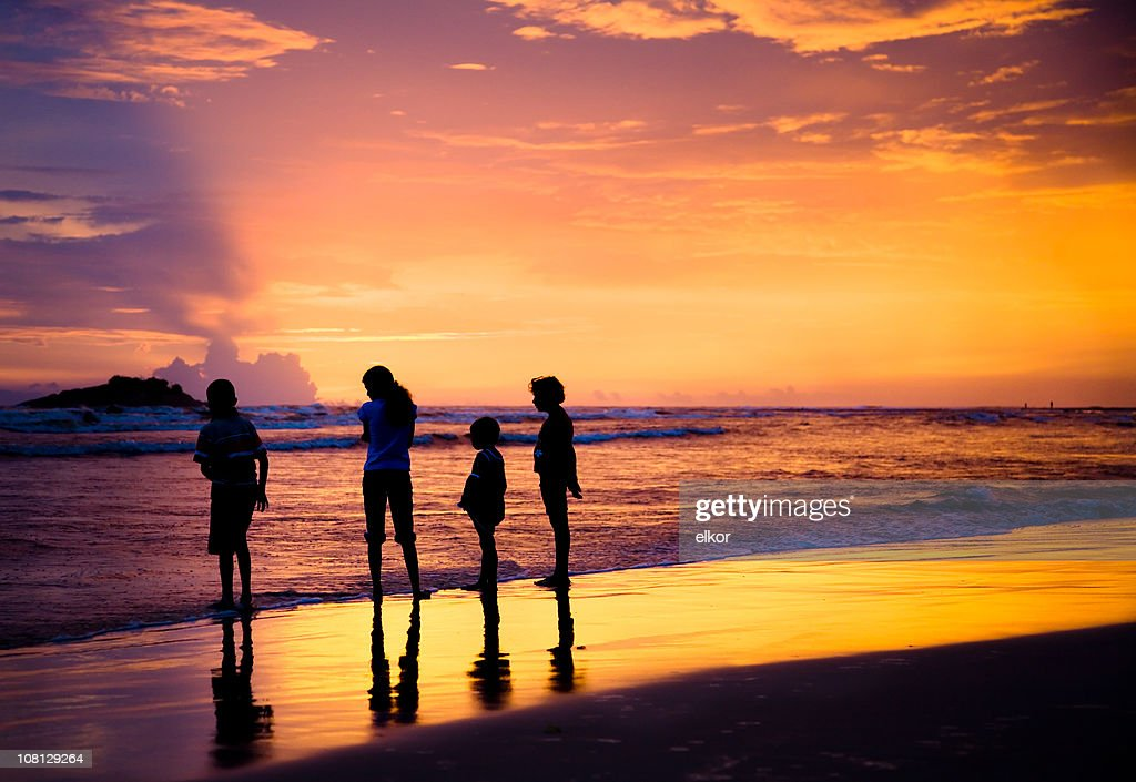 Silhouette Of Four Children On Beach At Sunset Stock Photo ...