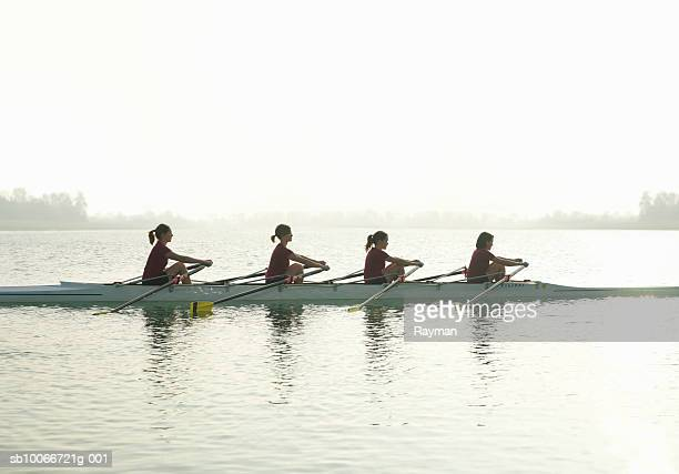 Silhouette of four females rowing, side view