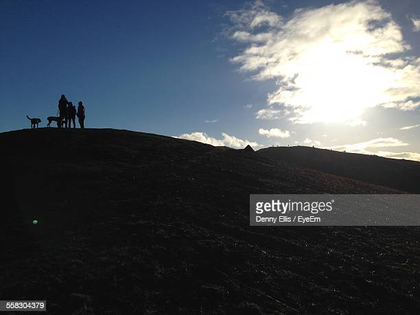 Silhouette Of Friends On Hill
