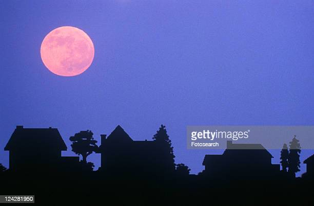 Silhouette of full moon over family homes in typical neighborhood