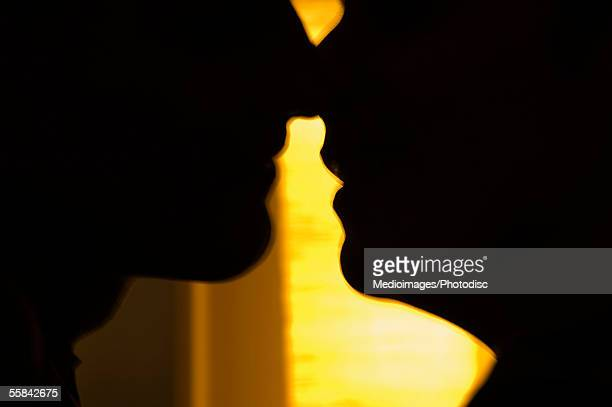 Silhouette of gay male couple about to kiss, close-up