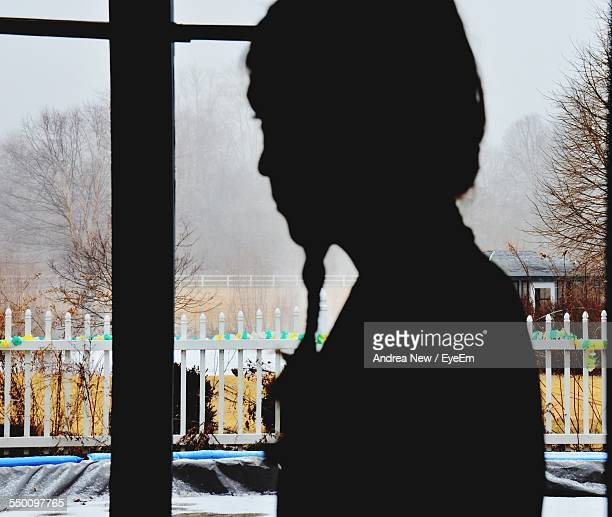Silhouette Of Girl Looking Out Of The Window